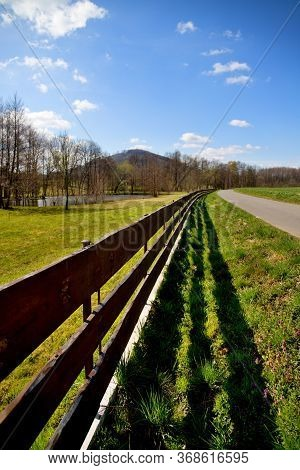 Wooden Fence Made Of Planks Lined With Path, In The Greenery, In The Background White Mountain, Blue