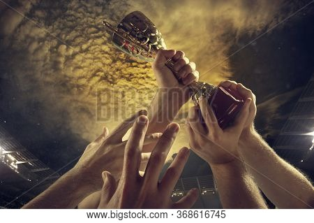 Leader Way. Award Of Victory, Male Hands Tightening The Golden Cup Of Winners Against Cloudy Dark Sk