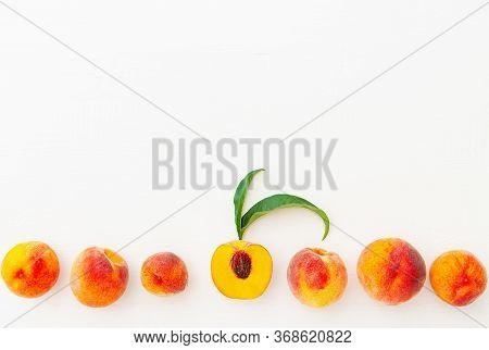 Peaches And Peach In Halves With Leaves On White Wooden Background. Flat Lay Composition With Ripe J