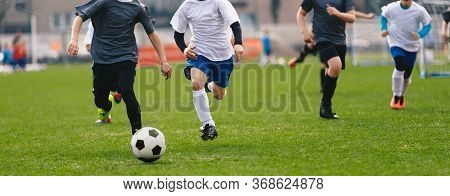 Kids Kicking Soccer Ball. Running Soccer Football Players. Four Junior Footballers On Duel. Football