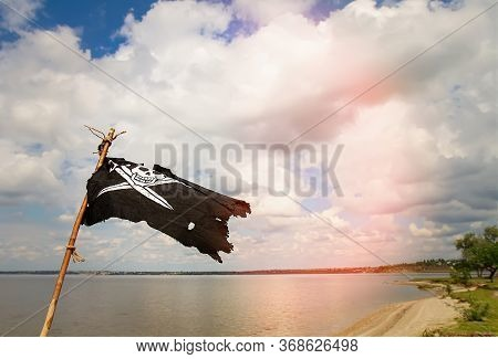 Black Torn Pirate Flag Jolly Roger With Crossed Sabers Waving On A Stick Against The Background Of T