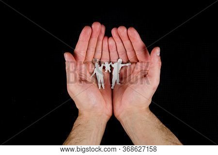 Protect Your Family Like An Eye In Your Head. A Man Holds In His Hands The Silhouette Of A Family -