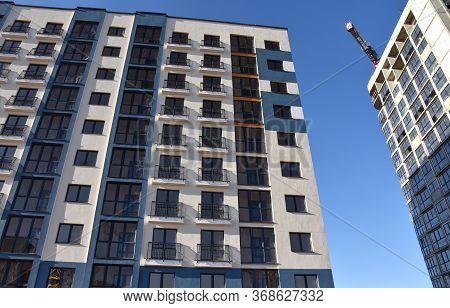 Construction Of A New Multi-storey Building. The Facade Building With Windows And Balconies. The Fra