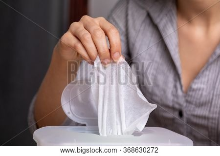 Wet wipes are universal an practical: woman hand take one wipe from big plastic box package for cleaning, home, indoor