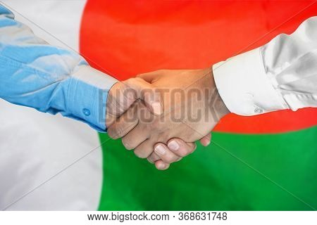 Business Handshake On Madagascar Flag Background. Men Shaking Hands And Madagascar Flag On Backgroun