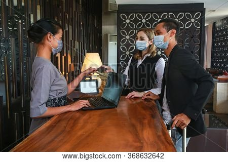 Couple And Receptionist At Counter In Hotel Wearing Medical Masks As Precaution Against Virus. Young