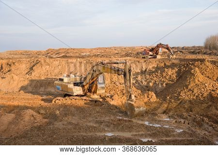 Excavators Working At Open-pit Mining. Backhoe During Earthworks On Sand Quarry. Earth-moving Heavy