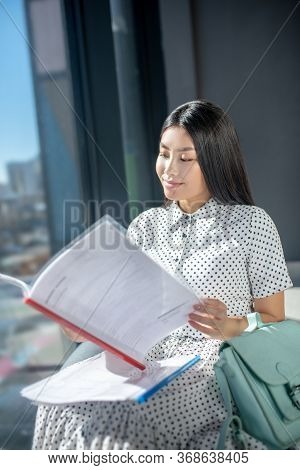Involved Young Brunette Female Sitting On Bag Chair, Looking Through Documents, Smiling
