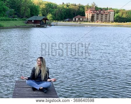 Lonely Girl Meditates Sitting Near A Lake And Smiles With Open Eyes In Lotus Position.