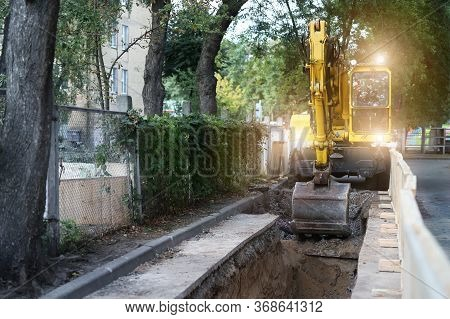 Big Modern Wheeled Excavator Digging Trench And Mowing Earth Layer At Infrastructure Heating Line Co