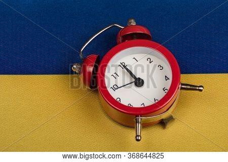 Ukrainian Flag And Vintage Alarm Clock Close Up. Time To Learn Ukrainian. Time To Travel Around Ukra