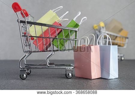 Paper Shopping Bags  In A Shopping Cart On Granite Floor And Grey Wall,e-commerce Or Electronic Comm