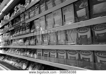 Black And White Image Of Different Types Of Cheese On Shelves In A Grocery Store. Shelf Of Packaged