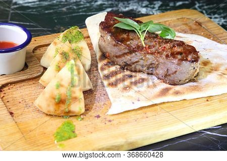 Medium-roasted Steak Cut Into Pieces On A Wooden Board With Sauce And Seasonings. Delicious Steak. B