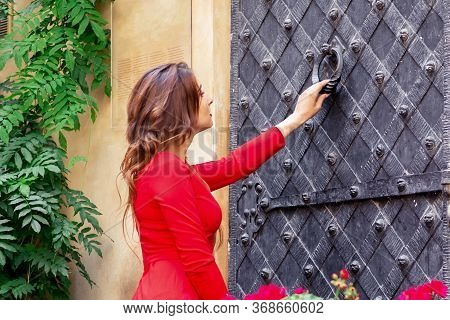 Young Woman Knocks On The Big Ancient Iron Door Standing Outside.