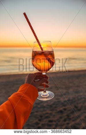 Girl Holding Glass Of Drink On Beach At Beautyfull Romantic Sunset. Glass And Hand Close Up