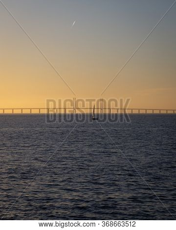 A Single Sailing Boat Is Out On The The Calm Ocean Between Denmark And Sweden During Sunset With The