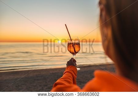 Girl Holding Glass Of Drink On Beach At Beautyfull Romantic Sunset. Glass And Hand Close Up. View Fr