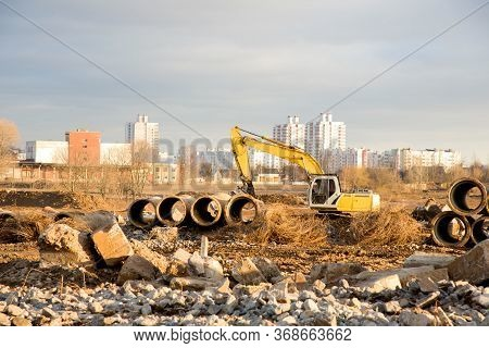 Excavator With Hydraulic Shears On A Construction Site Cuts And Crumbles Old Concrete And Asphalt. H