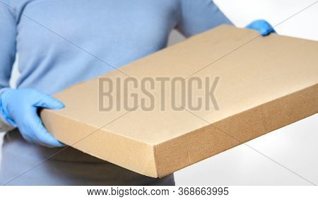 Person With Surgical Gloves Who Brings Pizza Box  To The Door Or Office . Concept Regarding Hygiene