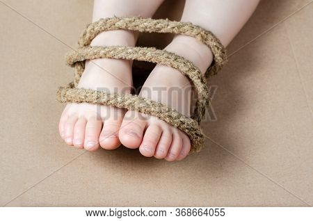 Child  Legs Tied With A Rope .concept Regarding Sexual Slavery .