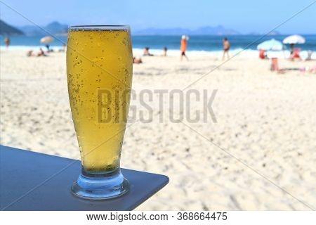 Glass Of Cold Draft Beer Against Sunny Copacabana Beach In Rio De Janeiro, Brazil, South America