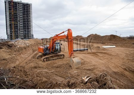Red Excavator During Earthworks At Construction Site. Backhoe Digging The Ground For The Foundation