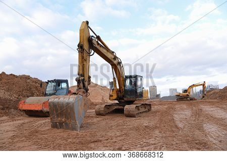 Yellow Excavator During Earthworks At Construction Site. Backhoe Digging The Ground For The Foundati