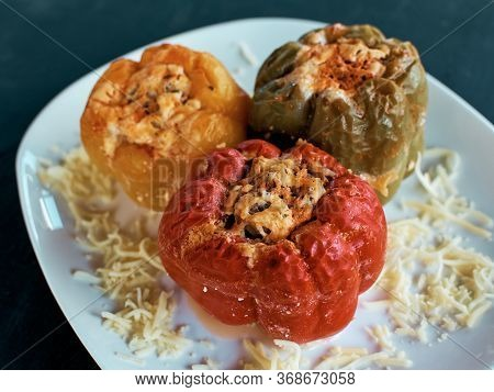 Stuffed Bell Peppers. Three Cooked Stuffed Peppers On A White Plate. Close-up. Juicy Peppers Recipe.