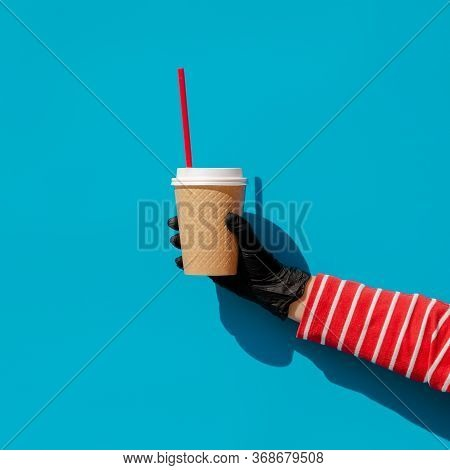 A Hand In A Disposable Glove Holds A Disposable Cup With A Drink And A Disposable Plastic Straw. Zer