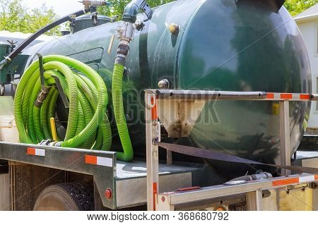 Sewage Tank Truck Pumping Machine Cleaning A Rental Mobile Toilet With Water Hose