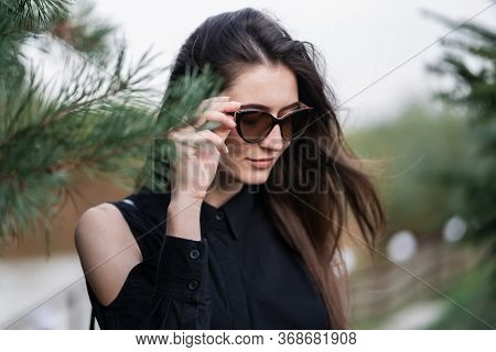 Beautiful Woman With Brunette Hair In Dark Clothes And Sunglasses. Fashion Street Photography. Fashi