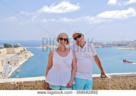 Middle-aged Couple Of Baby Boomers People Posing For Photograph Opposite Blue Sea In Valletta In Mal