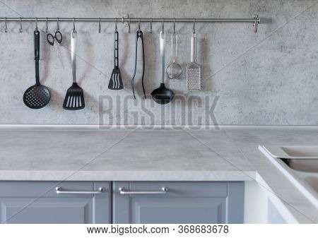 Kitchen Utensils Hang On A Crossbar In The Gray Modern Kitchen. Concept Of Homemade Interior With Ki
