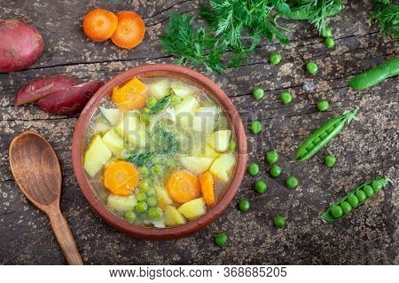 Spring Vegetable Broth With Peas, Potatoes And Carrots Served In A Clay Bowl. Healthy Vegan Broth Wi