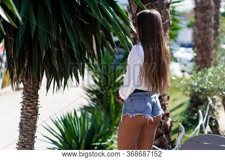 Beautiful Stylish Slim Girl Standing In A Tropical Park. Girl Wears Short White Shirt , Short Denim