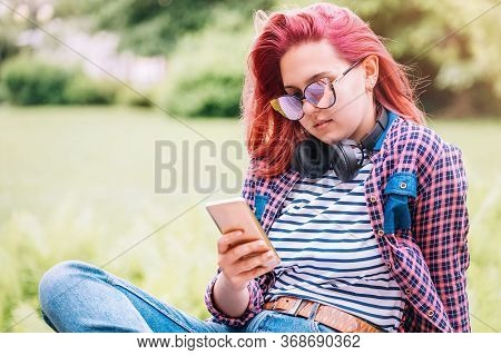 Beautiful Modern Smiling Young Female Teenager In A Checkered Shirt And Jeans With Headphones And Sm