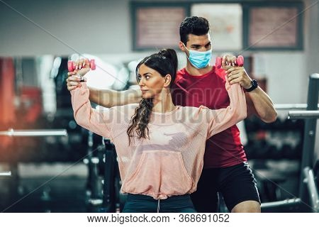 Young Beautiful Woman Doing Exercises With Personal Trainer. Man Wearing Face Mask