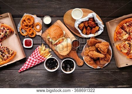 Table Scene With Large Variety Of Take Out And Fast Foods. Hamburgers, Pizza, Fried Chicken And Side