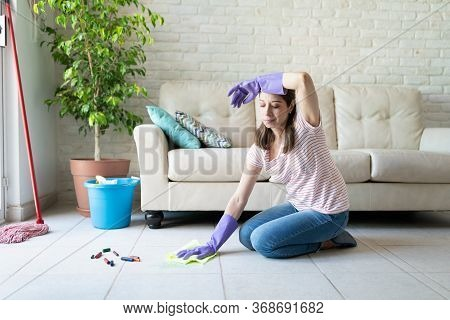 Tired And Overwhelmed Woman Wiping Sweat Of Her Forehead While Cleaning Her Children's Mess On The F