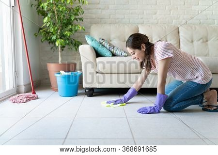 Attractive Caucasian Woman Kneeling On The Floor And Rubbing It With A Rag And Enjoying Cleaning Her