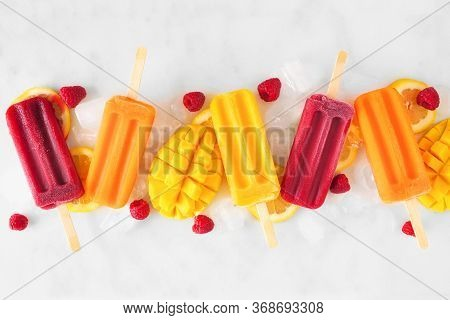 Group Of Assorted Summer Popsicles With Ice And Fruit. Overhead View In A Row On A White Marble Back