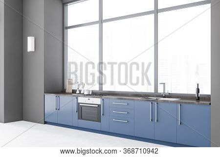 Corner Of Spacious Minimalistic Kitchen With Gray Walls, Concrete Floor, Blue Countertops With Built
