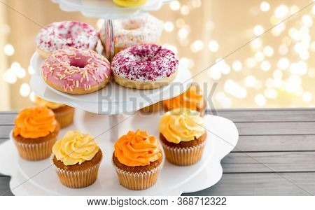 fast food and sweets concept - glazed donuts and cupcakes with buttercream frosting on stand over festive lights background