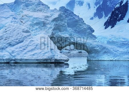 Snowing Floating Blue Iceberg Arch Reflection Mountains Paradise Bay Skintorp Cove Antarctica. Glaci
