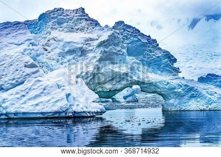 Snowing Floating Blue Iceberg Arch Reflection Paradise Bay Skintorp Cove Antarctica. Glacier Ice Blu