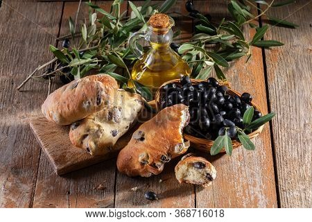 Traditional Italian Puccia Breads With Black Olives On A Cutten Board With Olive Oil And Olive Brach