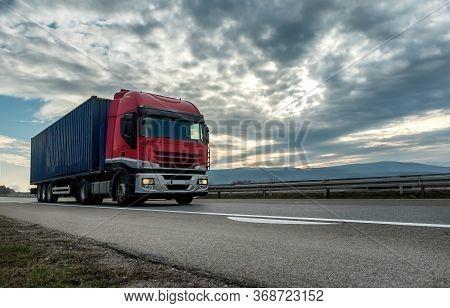 Red Transportation Semi Trailer Truck On A Highway Driving At Bright Sunny Sunset.   Transportation