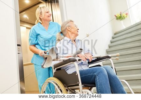 Old woman in a wheelchair at the elevator in a nursing home is cared for by a nurse