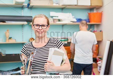 Art student with artist supplies in the painting shop or in the studio of the art academy